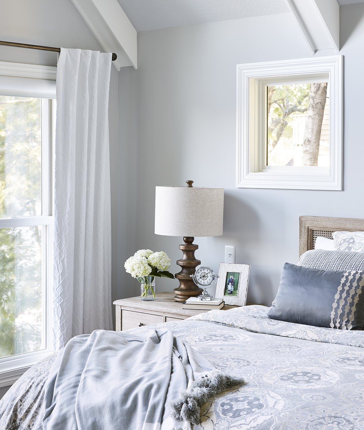 The simple masculine wood materials of the nightstand, headboard, and lamp pair seamlessly with the more feminine blue bedding in this spacious master bedroom. / Design by Sneak Peek Design