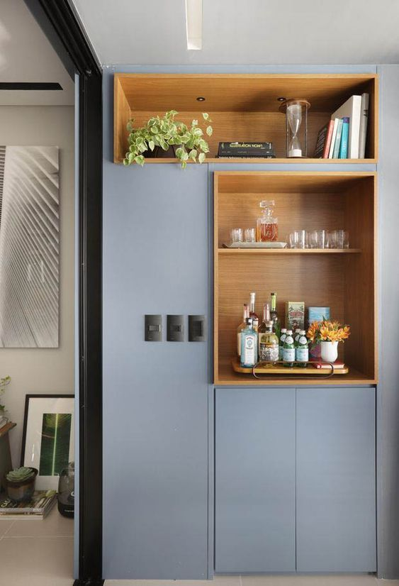 A modern built-in cabinet in this home office houses a complete bar set, including individual sparkling waters and cocktail fixings. / Source