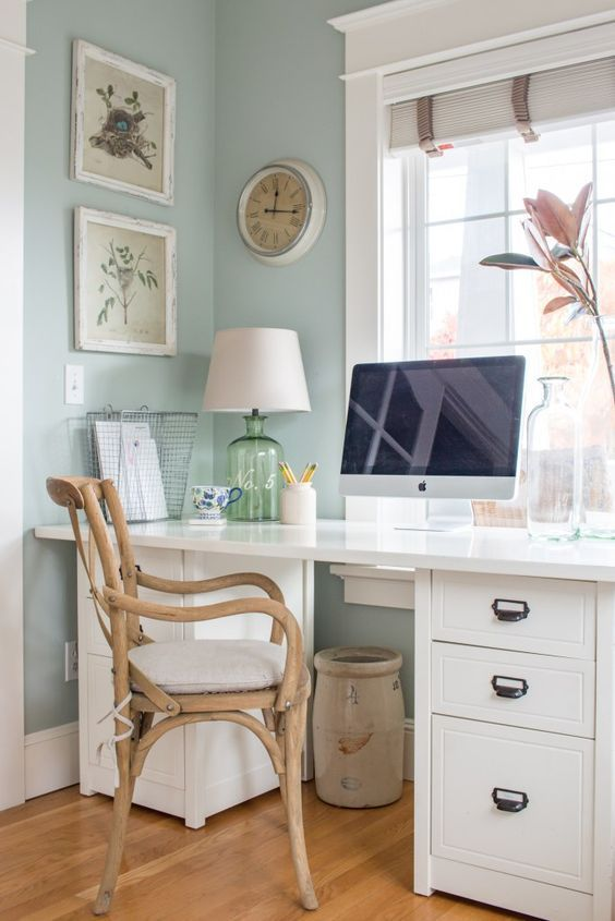 This home office keeps things light and bright with furniture in blonde wood and white, and a soft blue wall color. / Source
