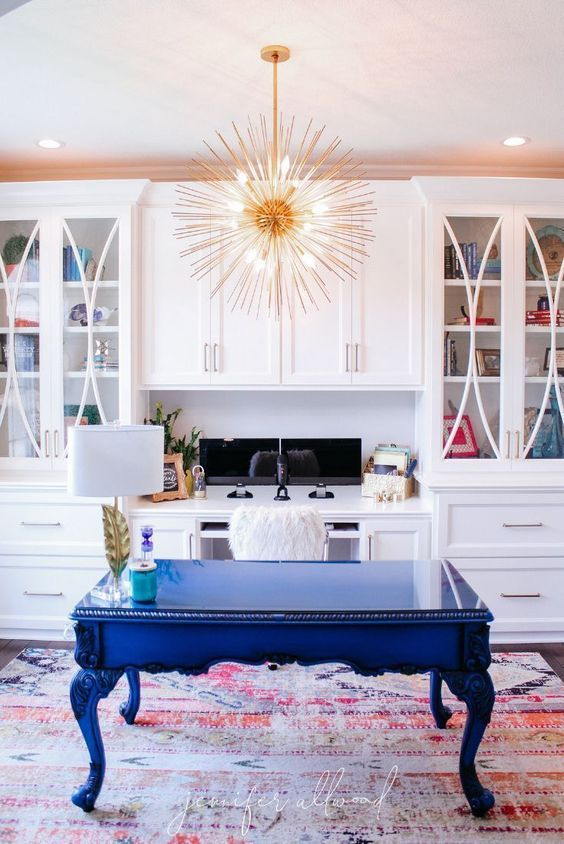 Blue is in for 2020 thanks to Pantone's Classic Blue color of the year, and this colorful home office uses it perfectly. The combination of a bright blue desk with a patterned pink rug and sleek white cabinets makes for an all-around trendsetting look. / Source