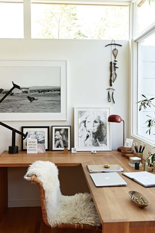 Artwork and personal photos sit alongside office supplies, making this workspace feel both chic and homey. / Source