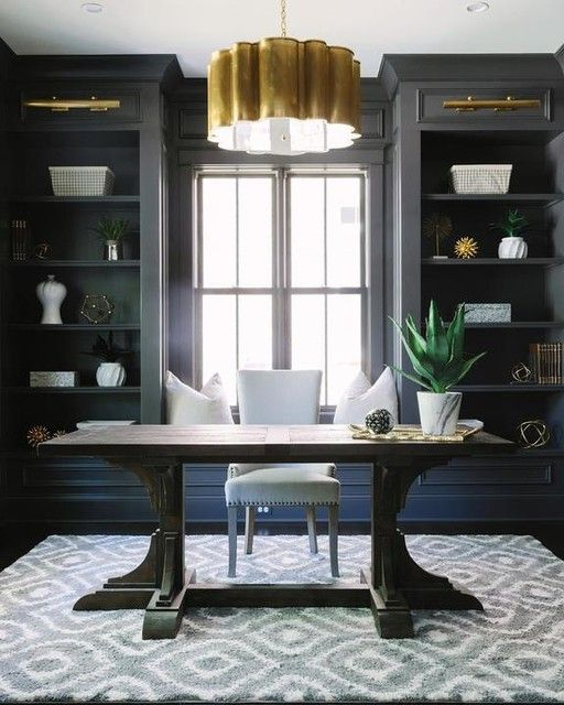 An office fit for a glamour-loving CEO, this space pairs moody charcoal built-ins with brass light fixtures and a chic grey area rug. / Source