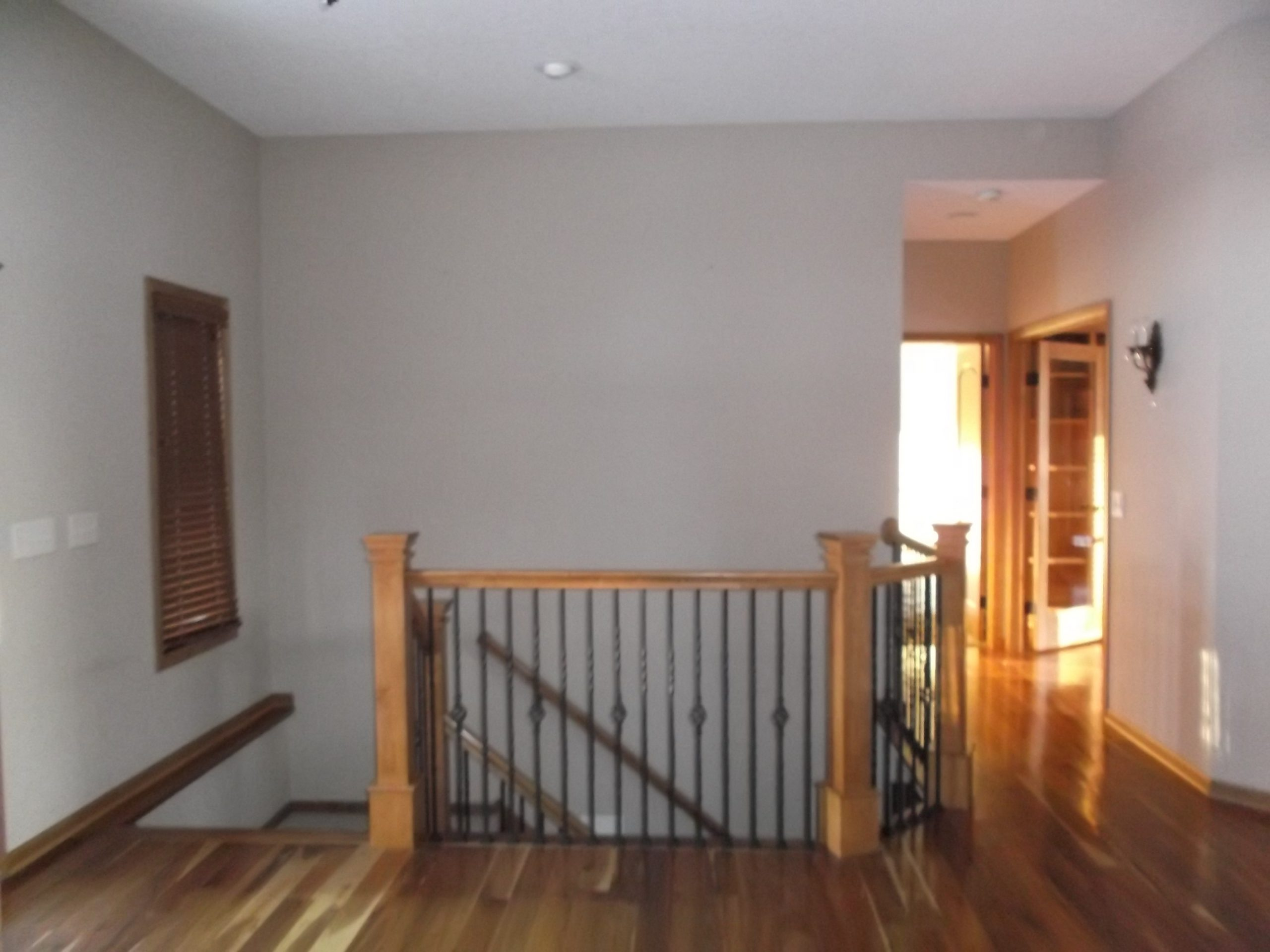 With 90s-style wood stain and busy ornamental iron bannister bars, this stairwell down to the lower level felt outdated, and the recessed light fixture above the steps was far too minimal for the space's needs.
