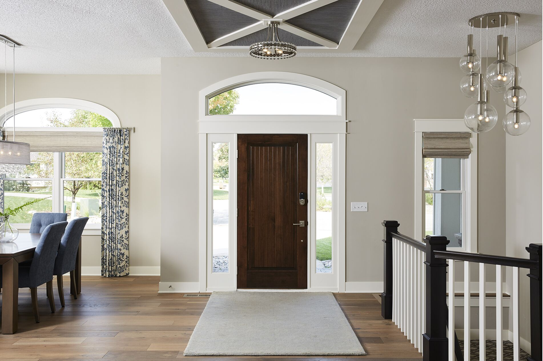 An open concept entryway welcomes guests with an array of complementary neutrals, crisp materials, and sleek light fixtures.