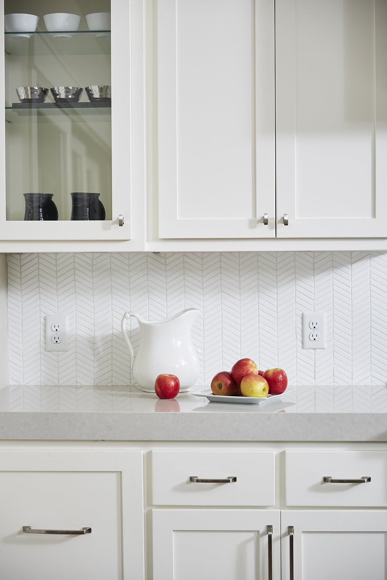 A bright white herringbone tile backsplash added subtle texture and interest to the space, popping against the grey countertops.