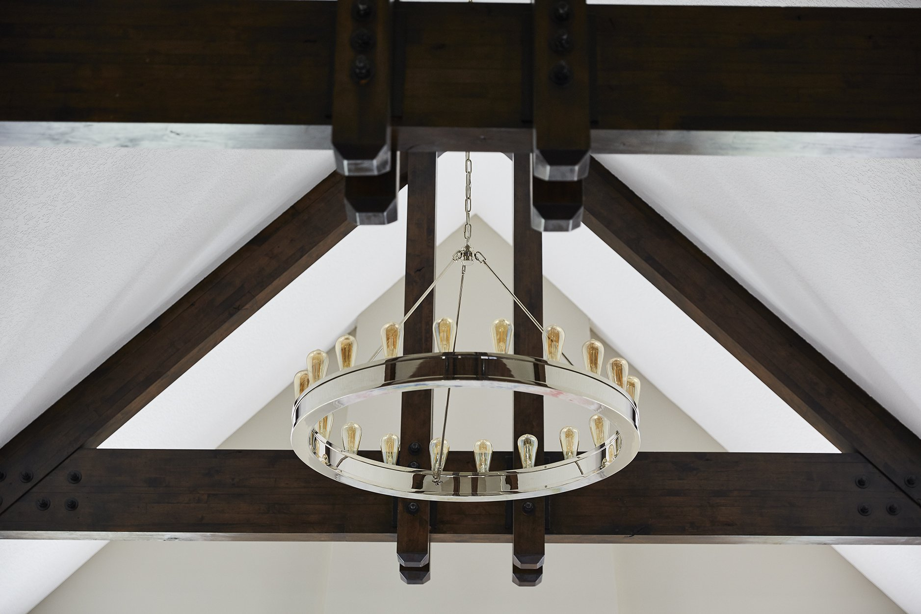 This modular ring chandelier by Ralph Lauren for Visual Comfort perfectly balanced a modern and traditional aesthetic, upgrading the look of the overall space and balancing out the grand ceiling.