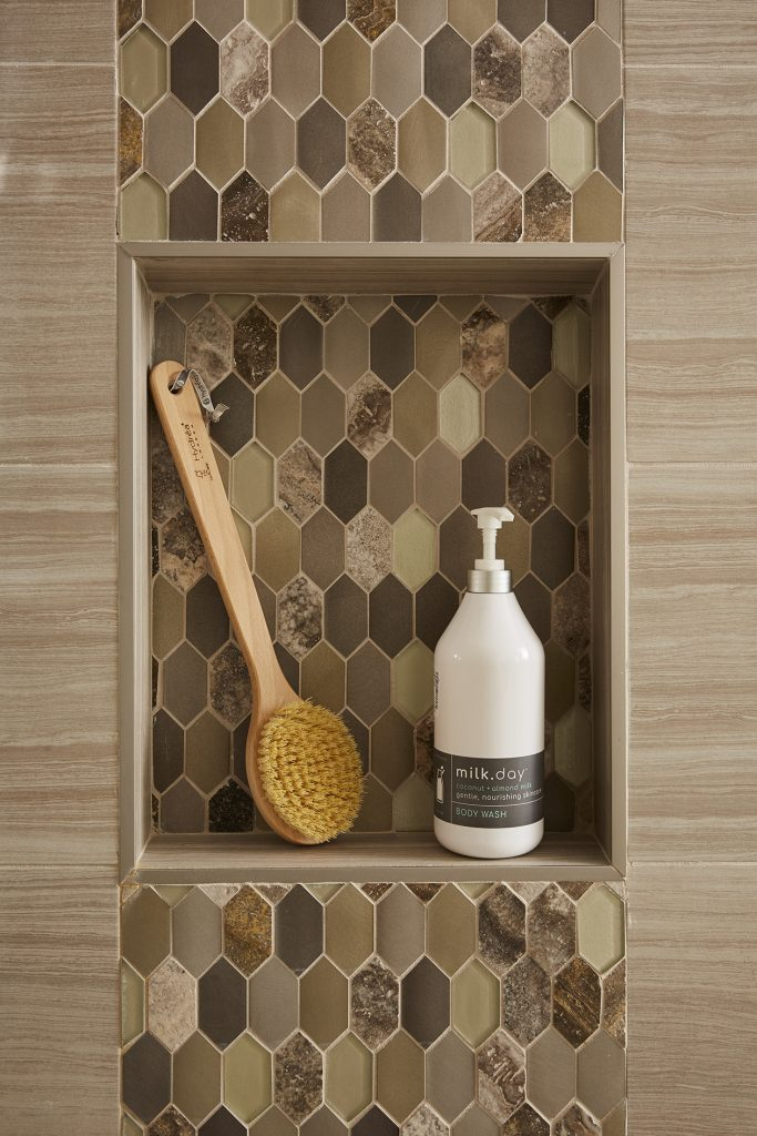 Beautiful tone-glass metallic hex tiles in a mix of browns and greys made this shower niche a beautiful and unexpected point of interest in the bathroom.