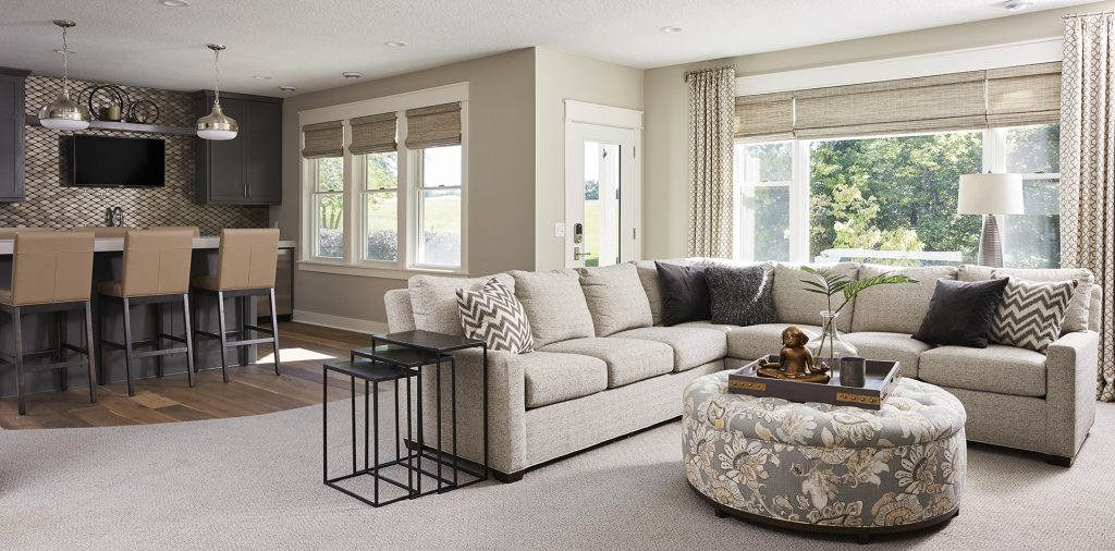 A metallic backsplash gives a modern flair to this neutral-based family room, and the open floor plan allows for a seamless transition between each space. (Interior Design: Carla Bast   Sneak Peek Design)