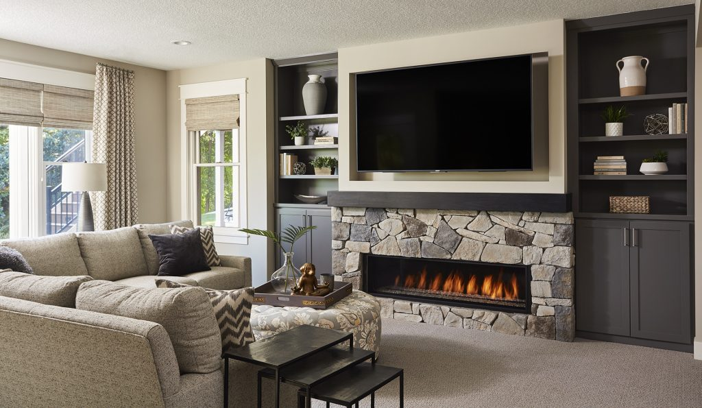This TV and fireplace feature wall includes two built-in cabinets to allow for ample storage and display space. (Interior Design: Carla Bast | Sneak Peek Design)