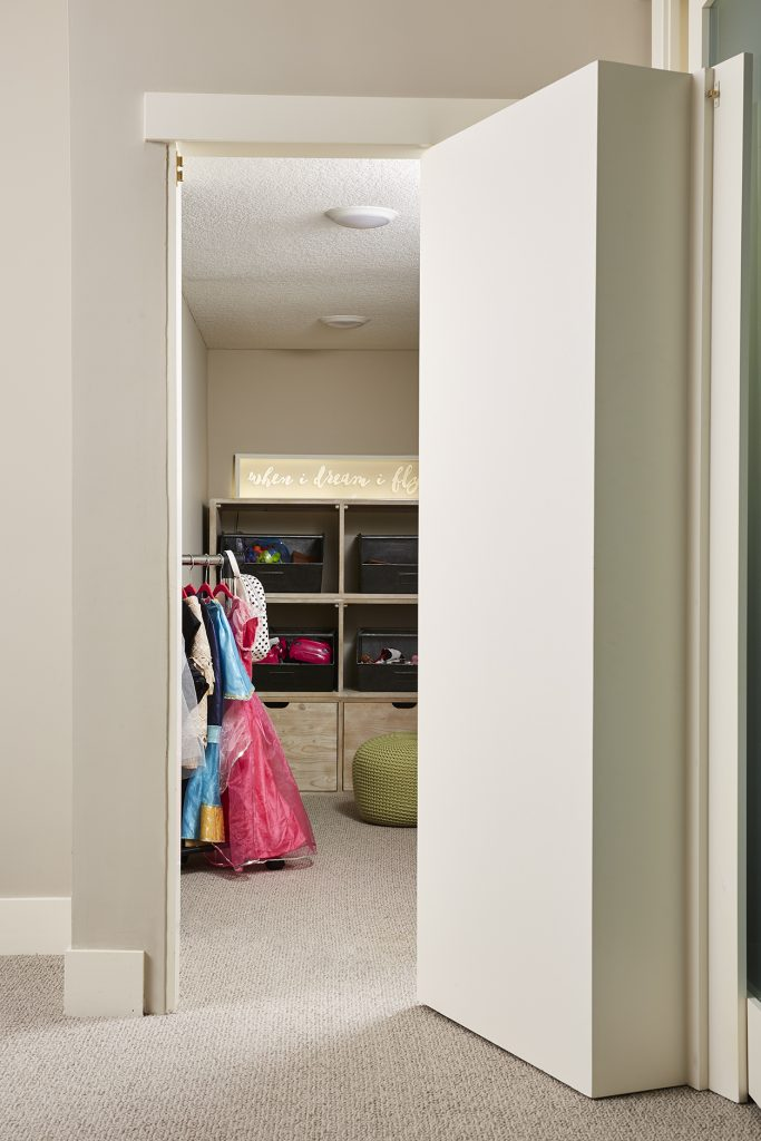 """Behind the bookcase is a """"secret"""" playroom for our clients' daughters. (Interior Design: Carla Bast   Sneak Peek Design)"""