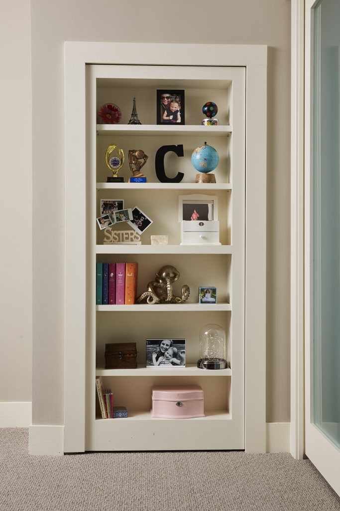 A hidden door disguised as a bookcase provides space to display beloved items and photos, adding a unique and playful decor touch to the room. (Interior Design: Carla Bast | Sneak Peek Design)