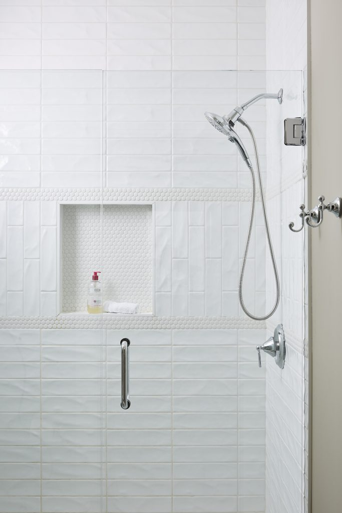 Gorgeous wavy textured subway tile helped this brand new shower feel chic and contemporary.