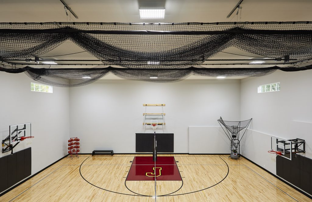A large sport court allows for plenty of space to play basketball for the entire family. (Interior Design: Carla Bast   Sneak Peek Design)