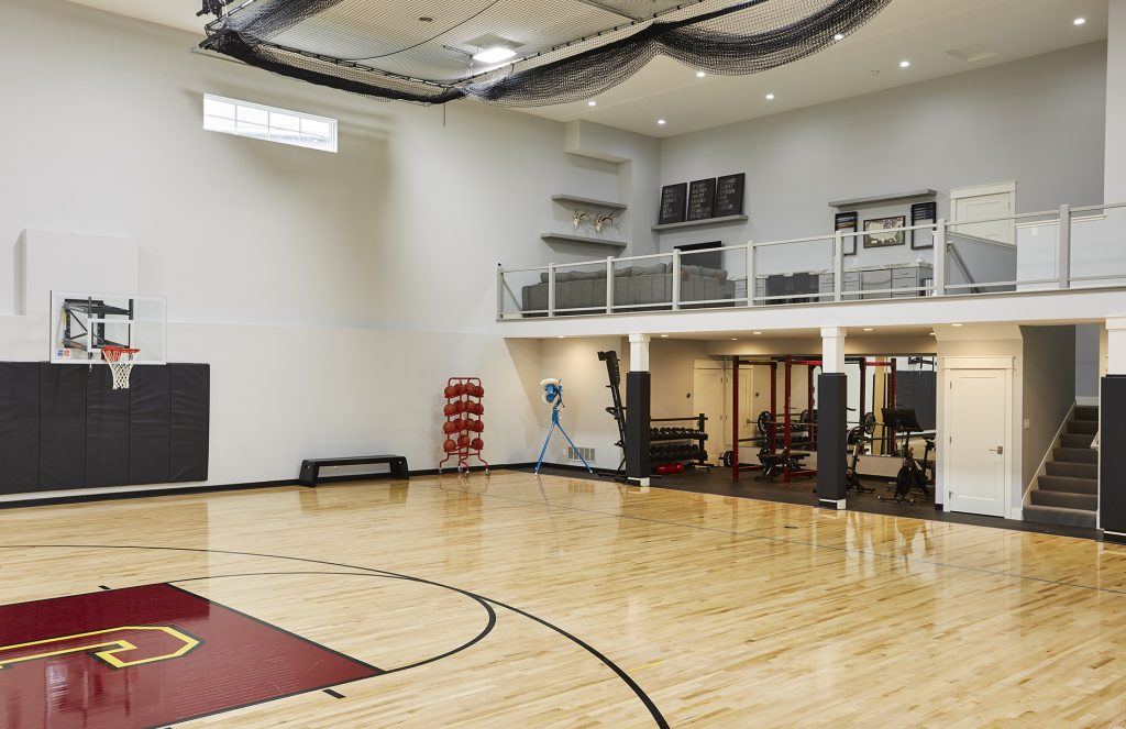 This sport court includes a weight and exercise room that makes it a cinch to stay in shape. (Interior Design: Carla Bast | Sneak Peek Design)