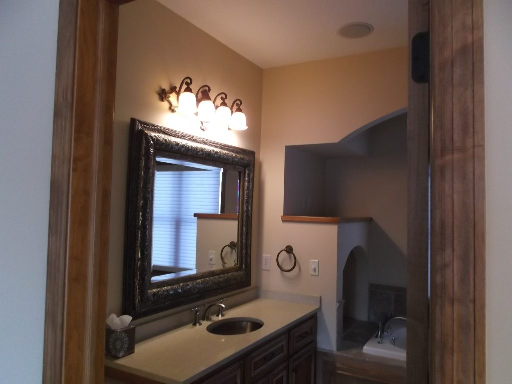 Built-in arches above the tub and to the right of the vanity gave this room an early-2000s design and simultaneously made the space feel smaller than it actually was.