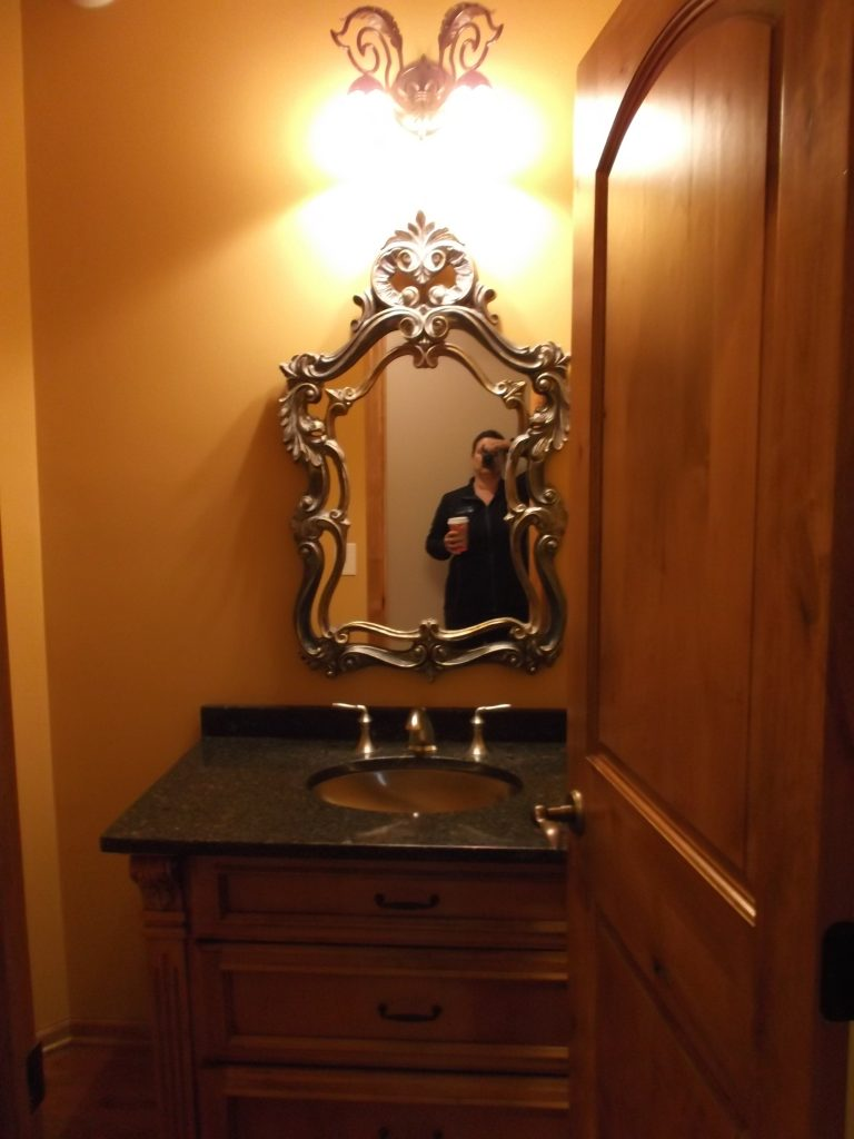 An ornate mirror and light fixture made this powder room feel firmly rooted in a traditional aesthetic.