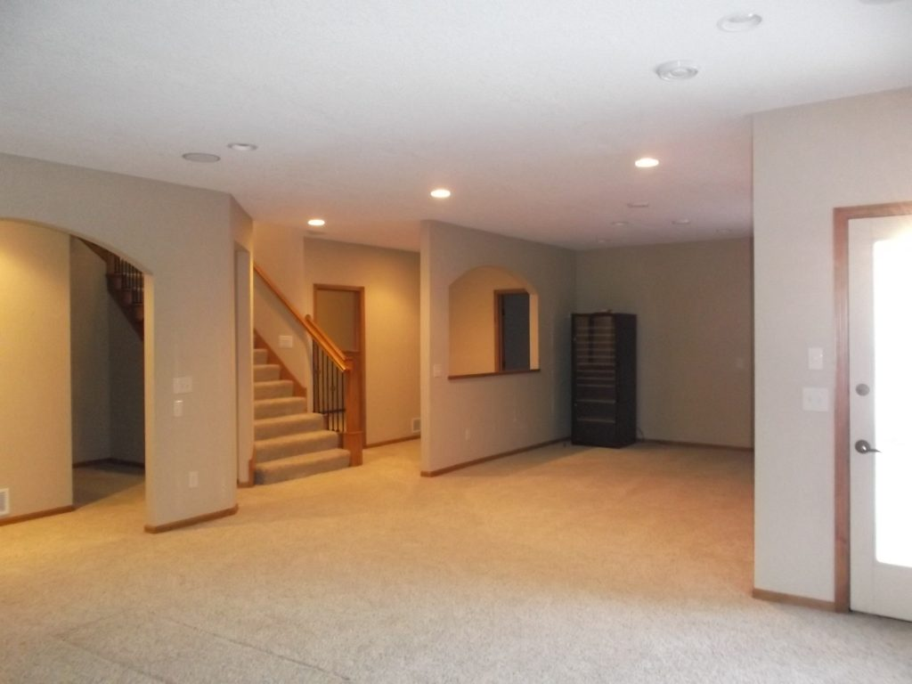 The multiple arched doorways in the original basement were created to conceal load-bearing posts, which posed a challenge. Additionally, the style felt outdated and too traditional for our clients' taste and lacked a wet bar.