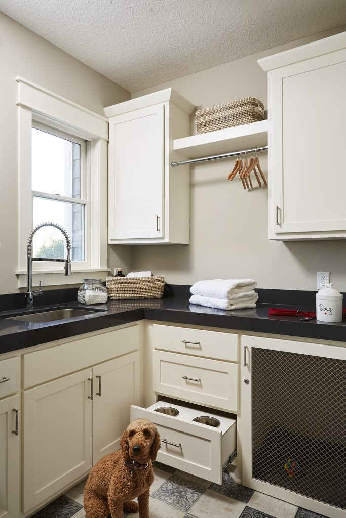 A new laundry room layout with custom cabinetry allowed for plenty of space to fold and store laundry while also designating spaces for everyday essentials like the dog food and kennel. (Interior Design: Carla Bast | Sneak Peek Design)