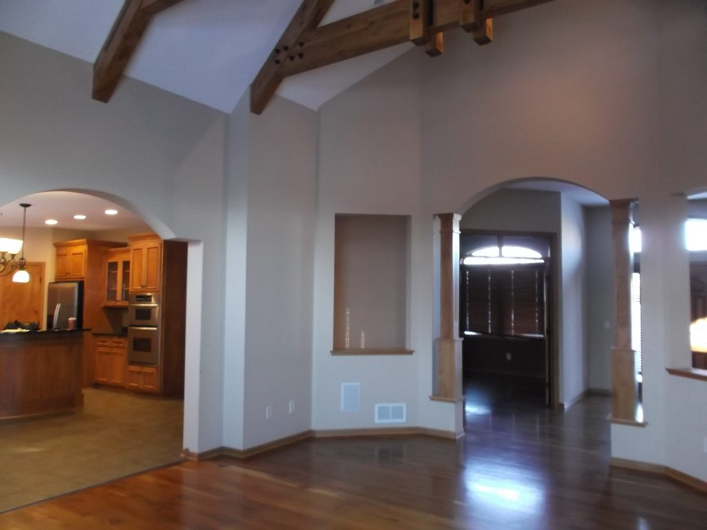 Multiple walls separated the living room from the kitchen and entryway, with outdated and unnecessary intricate combinations of arches, columns, and built-in nooks.