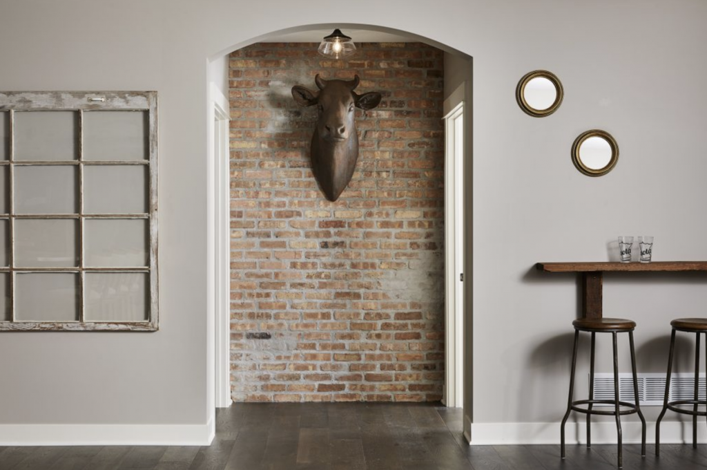 With warm infusions of brown and grey accents via brick, wood, and a faux taxidermy bull head, this basement's use of Anew Gray is charming and sleek. (Interior Design: Carla Bast | Sneak Peek Design)