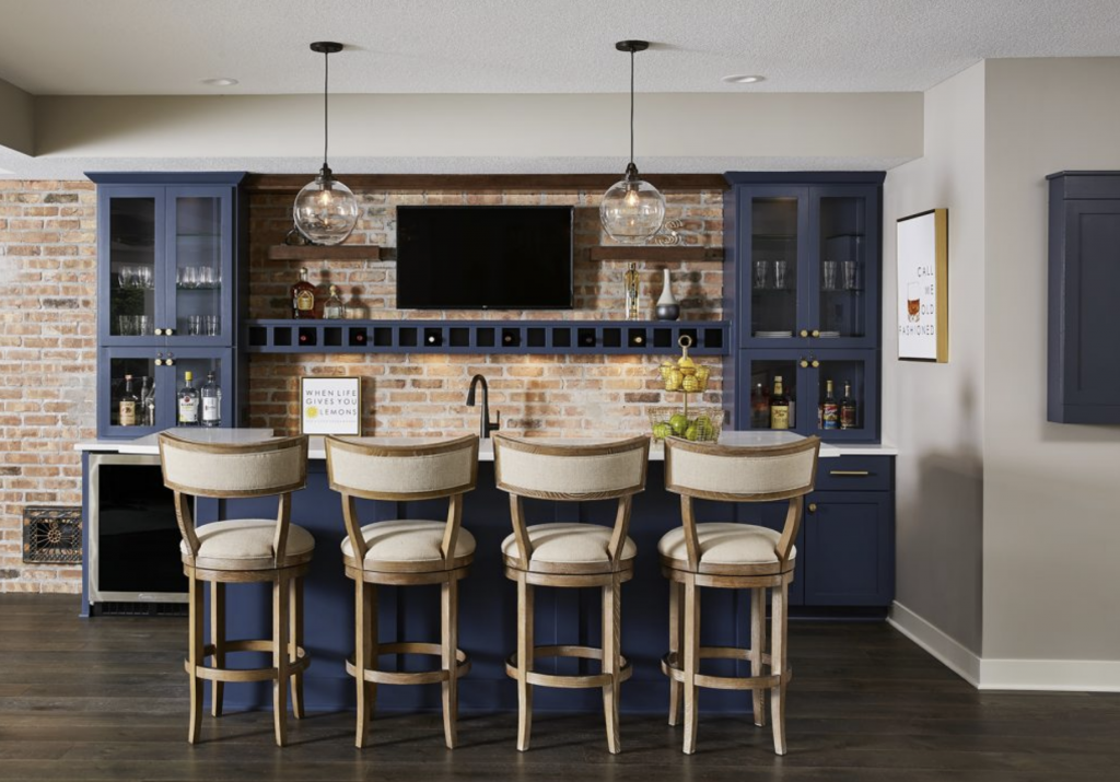 Sherwin-Williams' Anew Gray pairs perfectly with a bold blue basement wet bar and contemporary island seating. (Interior Design: Carla Bast | Sneak Peek Design)