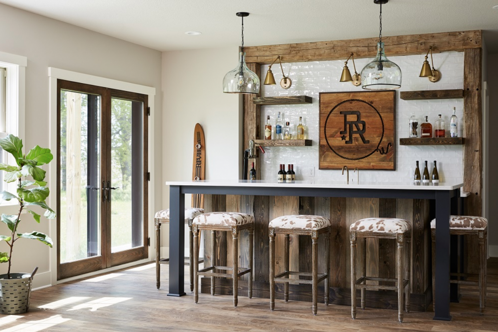 Paired with reclaimed wood and cowhide-upholstered stools, this basement bar stuns against walls painted in Benjamin Moore's Balboa Mist. (Interior Design: Carla Bast | Sneak Peek Design)