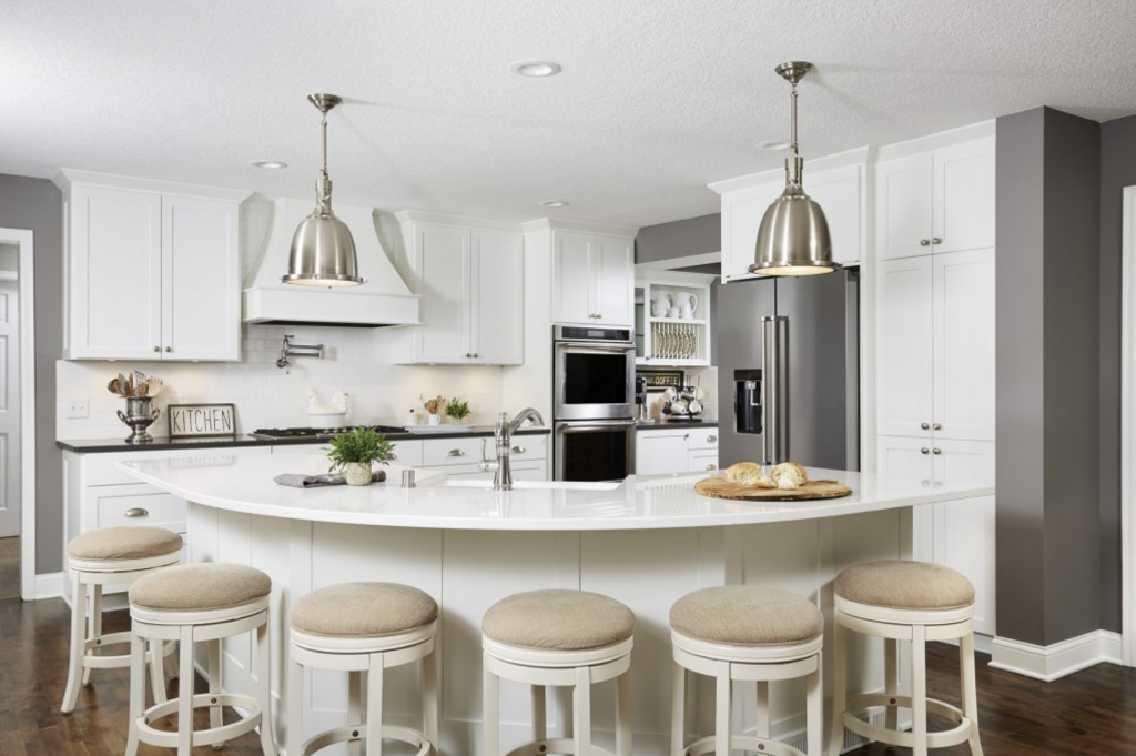 A large curved kitchen island offered so much more seating capacity than its previous set up, in addition to visually opening up the space between the kitchen and great room.