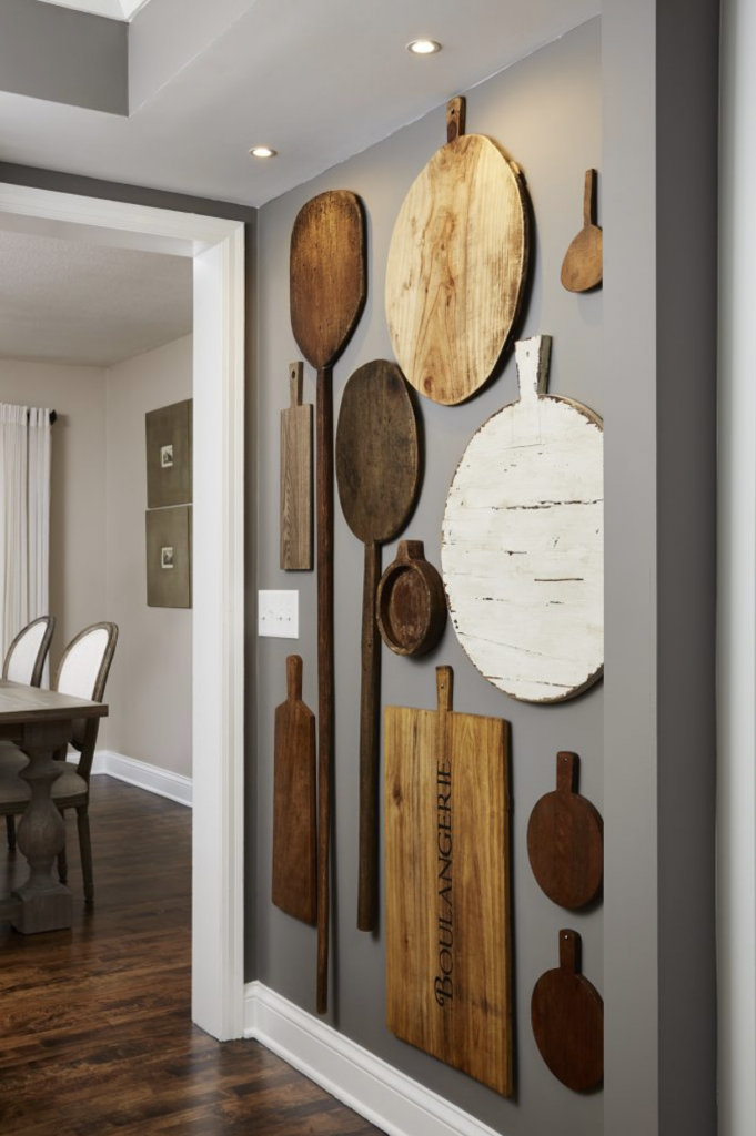 The now-opened up hallway between the kitchen and dining room became a new focal point, allowing for a unique display of our clients' vintage wooden boards and paddles.