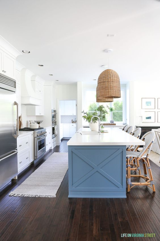 Paired with a large blue kitchen island, this all-white space has the perfect balance of neutrals and color infusion. (Credit: Life on Virginia Street)