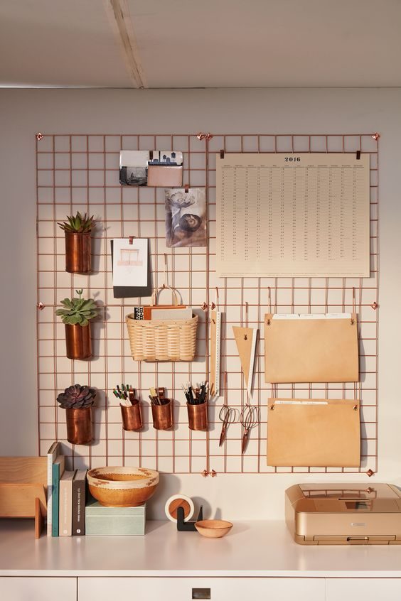A bold metallic wire board makes organization a snap in this home office, and with several hanging potted plants, it provides a stylish zoom backdrop.