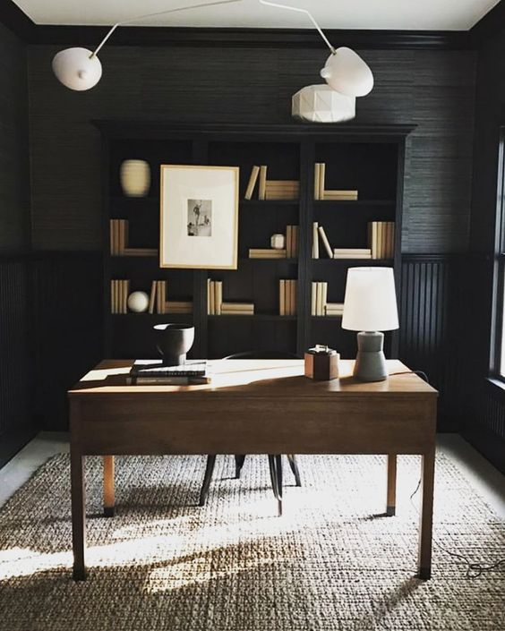 Built-in shelves give this dark and moody home office an area to add visual contrast with white and cream books, art, and figurines layered together.