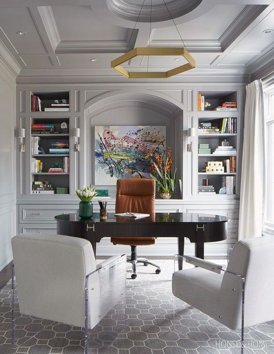 With a large-scale painting anchoring the wall, the surrounding bookcases on either side help to add pops of color here and there, turning this grey-based office into a beautiful and homey space.