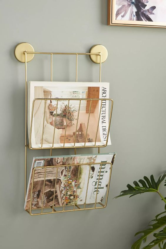 A sleek gold magazine rack is the perfect accessory to add to an organized and beautiful background wall.