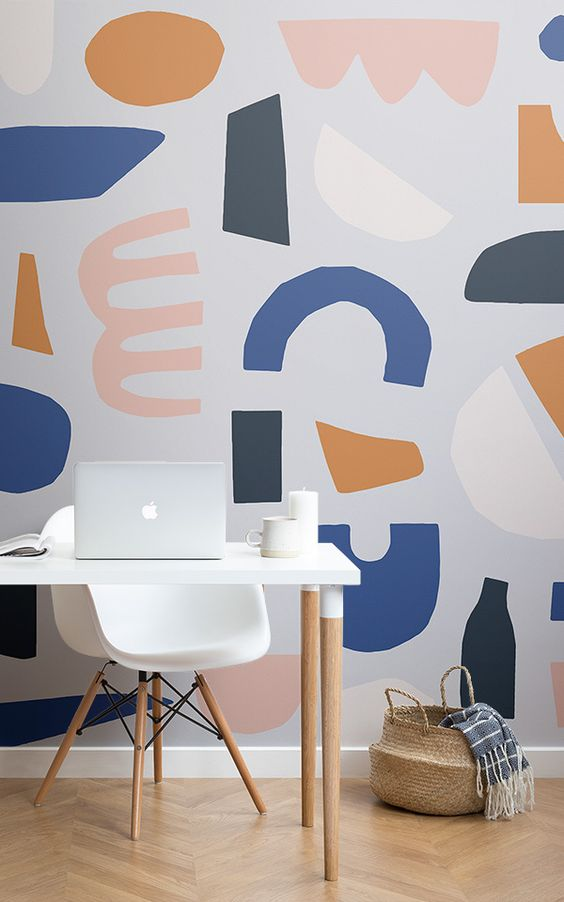 Geometric shapes either painted directly onto the creamy white wall or used within a wallpaper design provide visual interest, and in this small and compact home office, they make the simple white and wood desk pop.