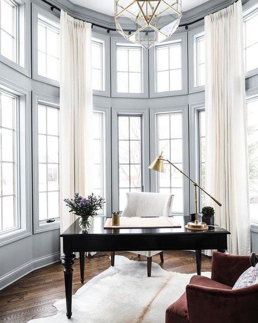 Floor-to-ceiling windows stun in this spacious and glamorous home office, providing the perfect video backdrop for conference calls.