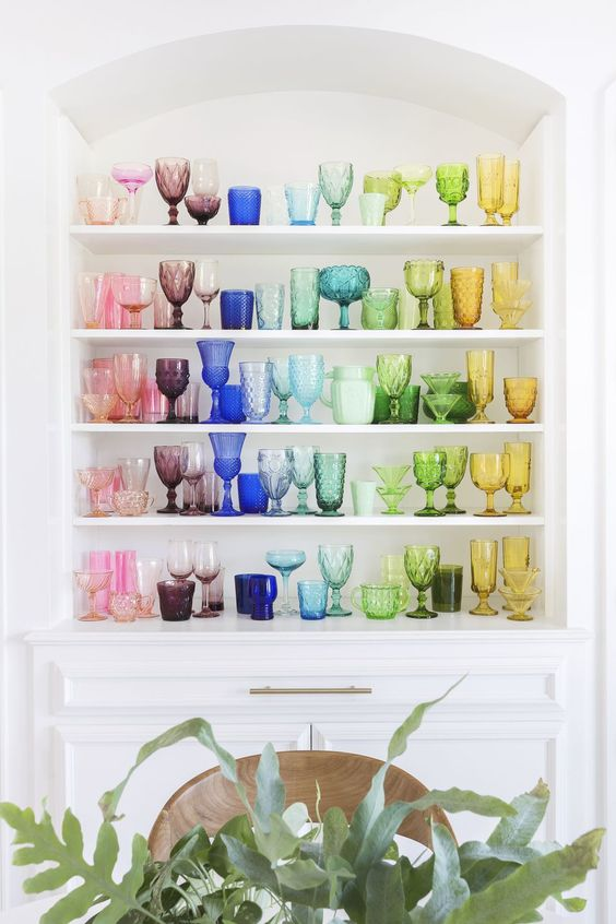 Colorful glassware arranged in groups adds a vibrancy to this otherwise-neutral space.