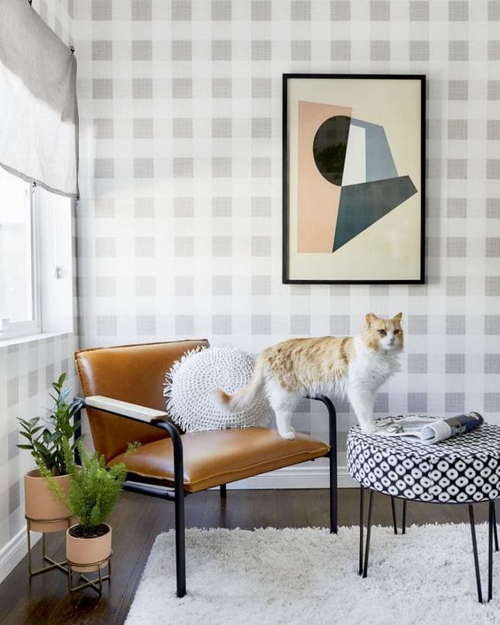 A neutral color palette shines in this home office thanks to the plaid wallpaper background behind this perfectly-cozy and zoom-friendly corner chair.