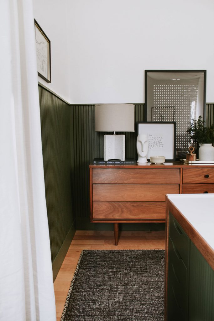 Deep green-painted beadboard adds depth and interest to this home office, and layered with neutral decor pieces, it's absolutely gorgeous.