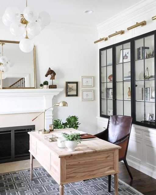 A former built-in hutch becomes a space to display personal photos, mementos, and books in this stylish and sleek home office.