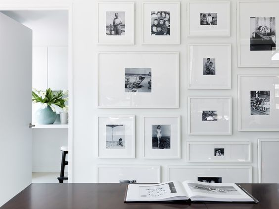 Family portraits get a stylish upgrade with matching white frames and a variety of shapes and sizes of their surrounding mattes.