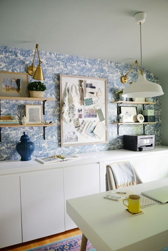A whimsical blue and white wallpaper brings this home office to life and provides an infusion of color that is simply delightful.