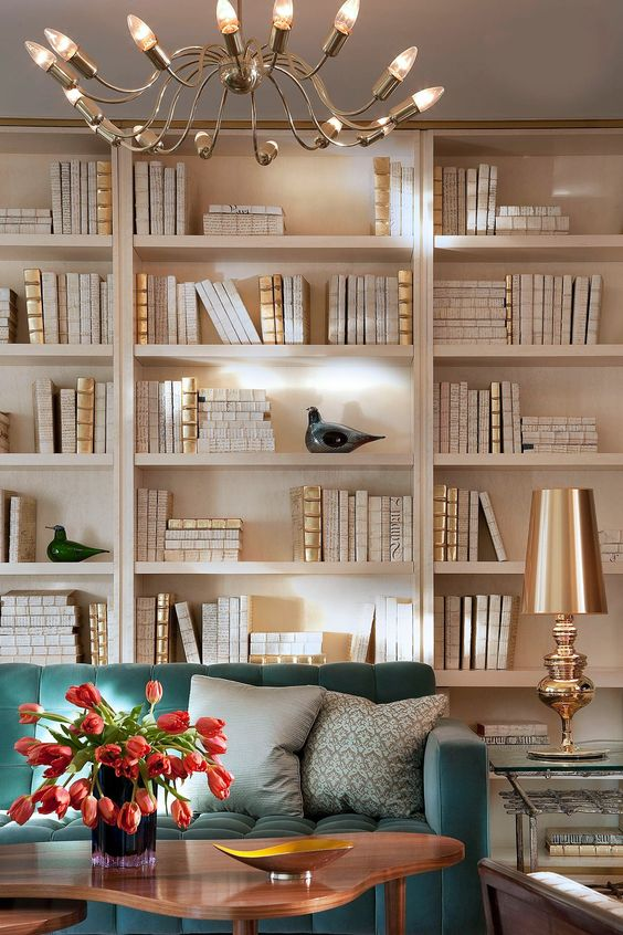 This home office allows the bold teal sofa to take center stage with a backdrop of all-neutral books and tchotchkes filling its built-in shelves.