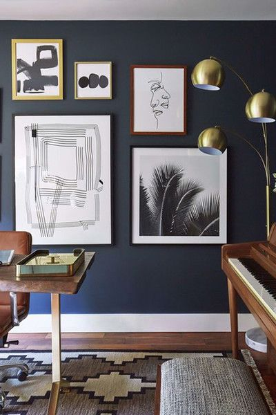A variety of art styles and sizes feel cohesive in this gallery wall thanks to the overarching black and white theme.