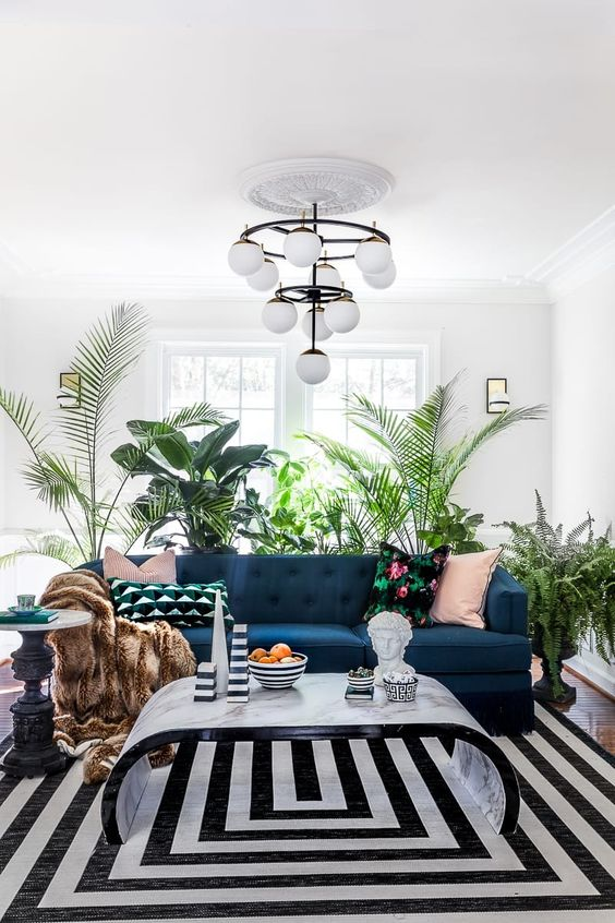 Embracing maximalist style, this living room relies on a backdrop of layered leafy plants to provide visual interest and a touch of exotic excitement.